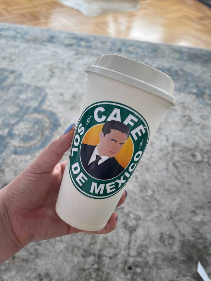 """The author holding the coffee cup that says """"Cafe Sol De Mexico"""""""