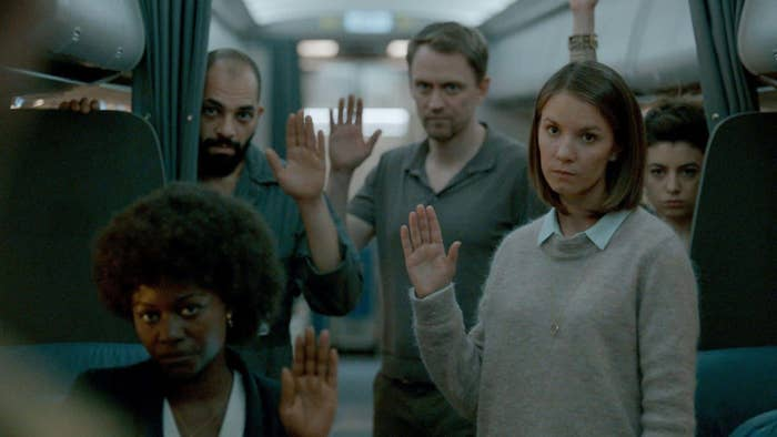 Several people raise their hand in unison while standing aboard a plane.