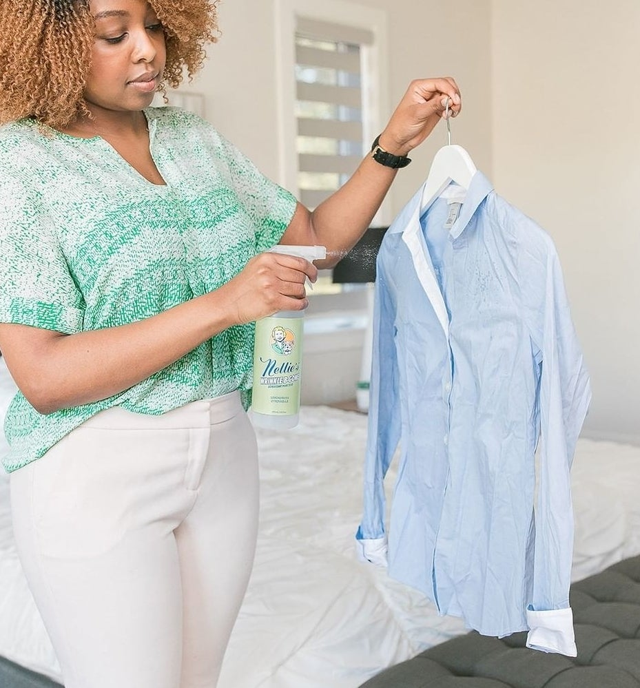 A person spritzing a wrinkled shirt with the wrinkle-releasing mist