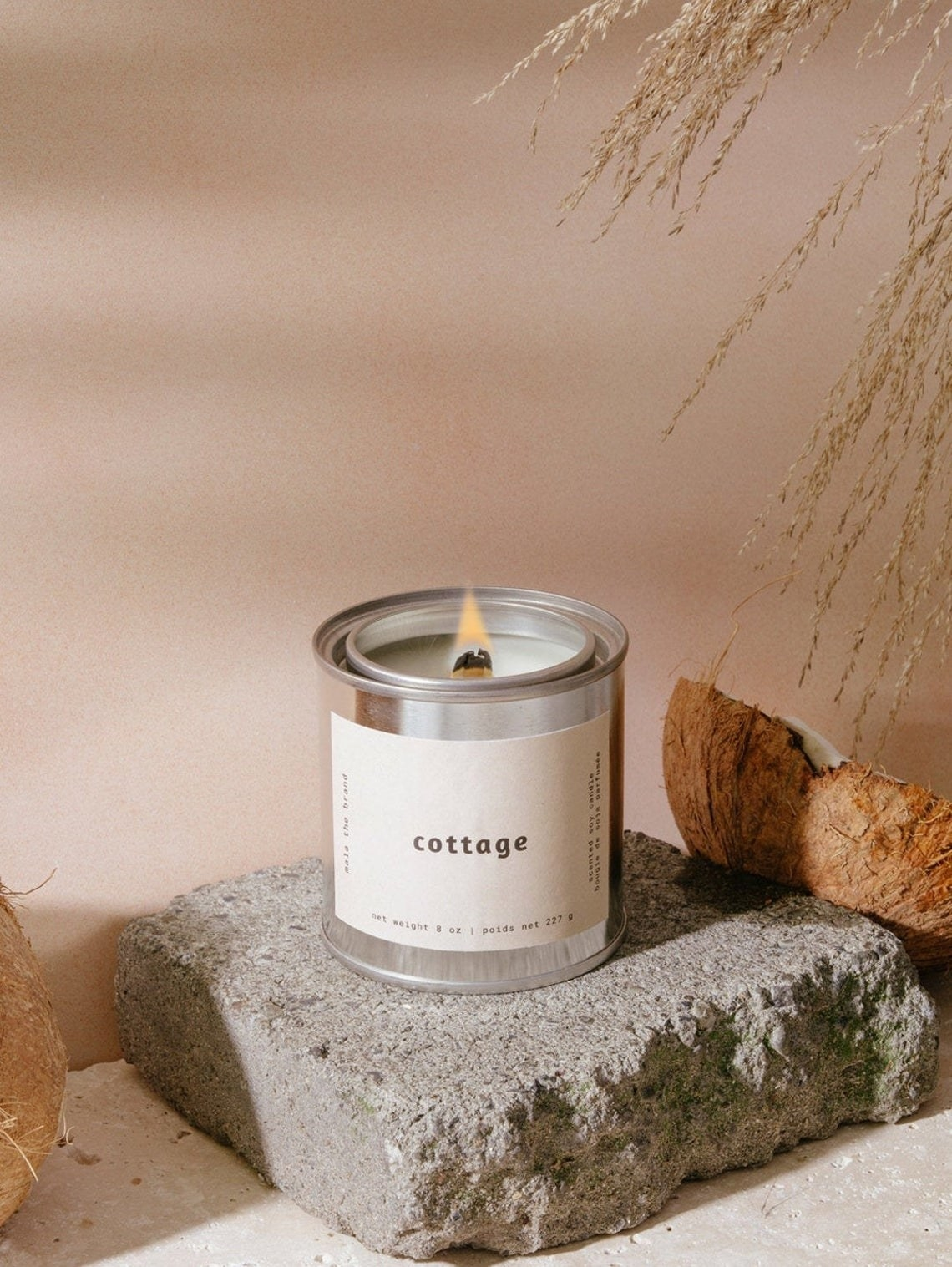 A lit candle in a metal tin
