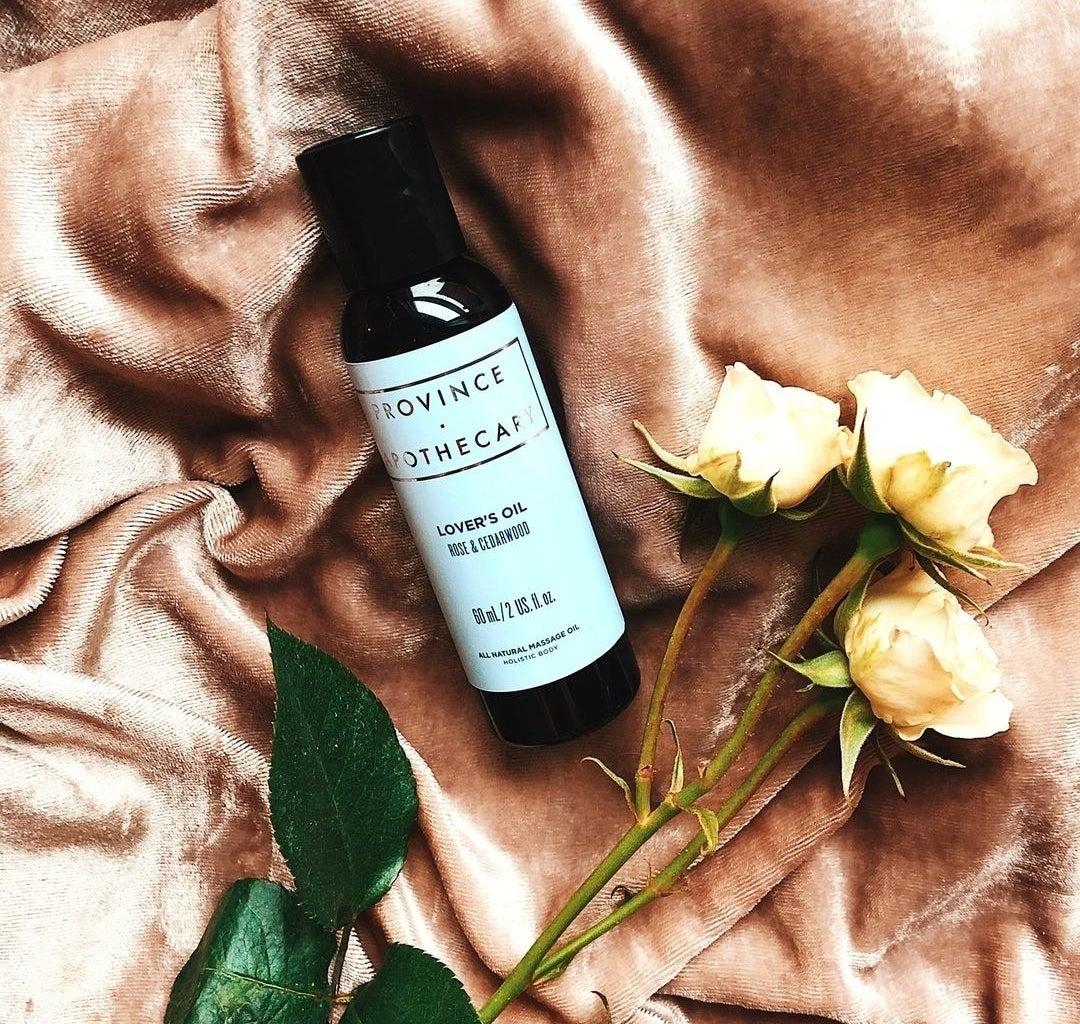 A bottle of massage oil on a velvet blanket
