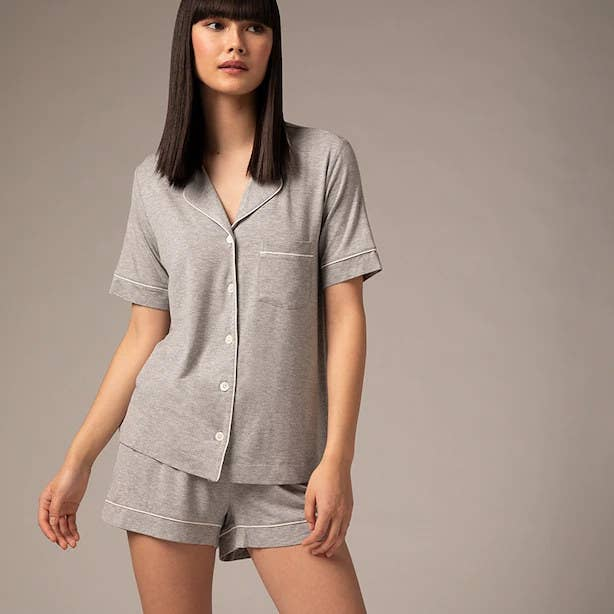 A person wearing a pyjamas shirt and matching shorts