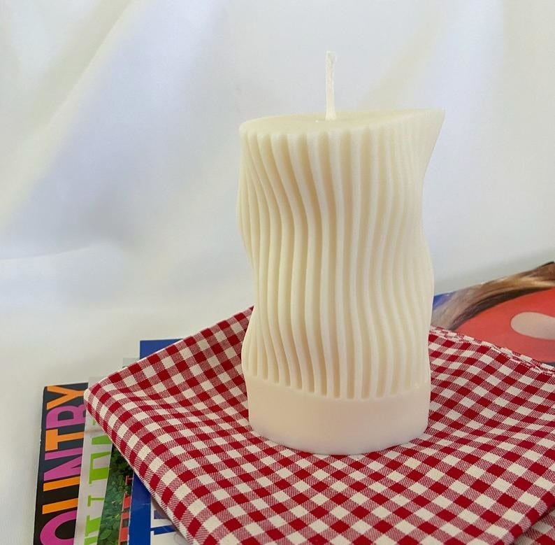 the white candle with vertical stripes and waves