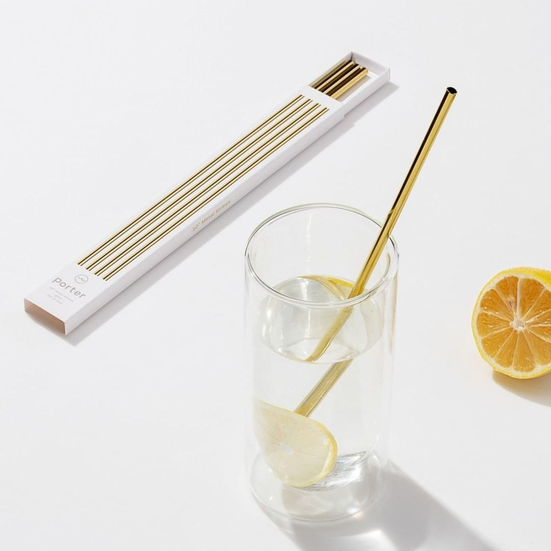 A set of metal straws on a counter next to a glass of lemon water