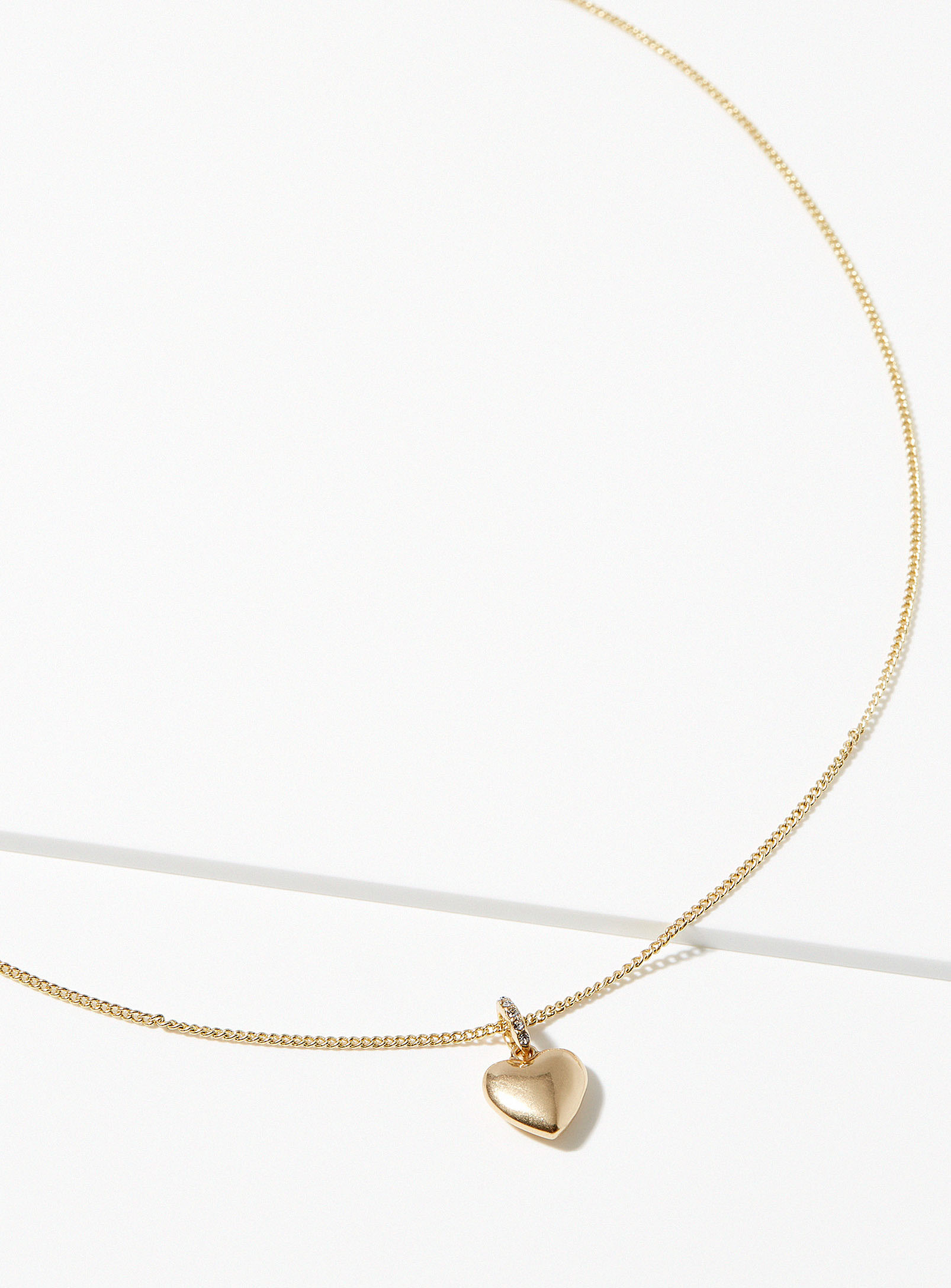 A gold necklace with a heart pendant