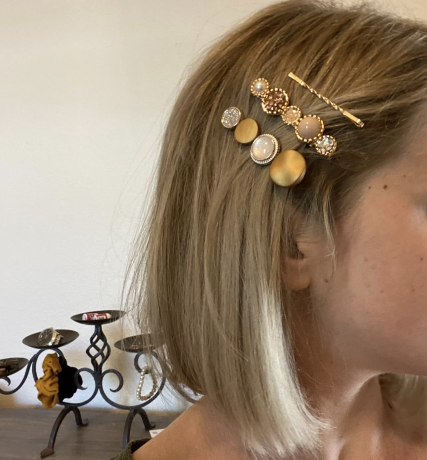 A person wearing three clips in their hair