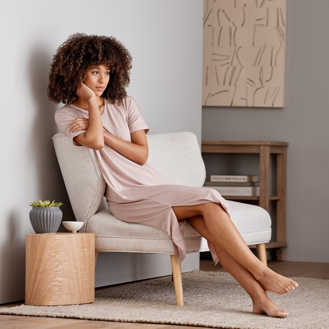 Someone lounging on a sofa while wearing the flowing t-shirt dress