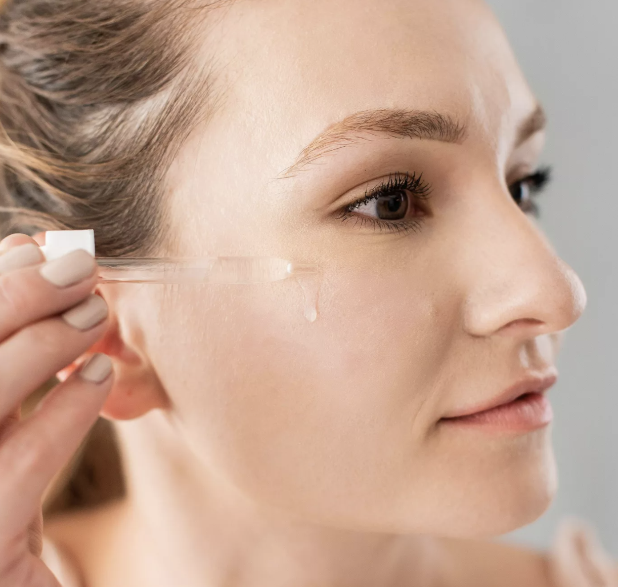 a model applying the serum to their face