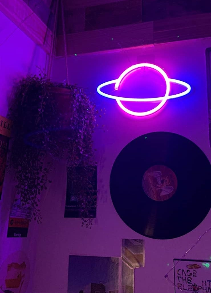 a reviewer's neon planet hanging on the wall