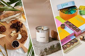 A round wooden tray with crackers, cheese, and fruit on it, A lit candle in a metal tin, Four large gift boxes filled with tea samples