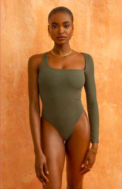 a model wearing the body suit in olive green with one long sleeve