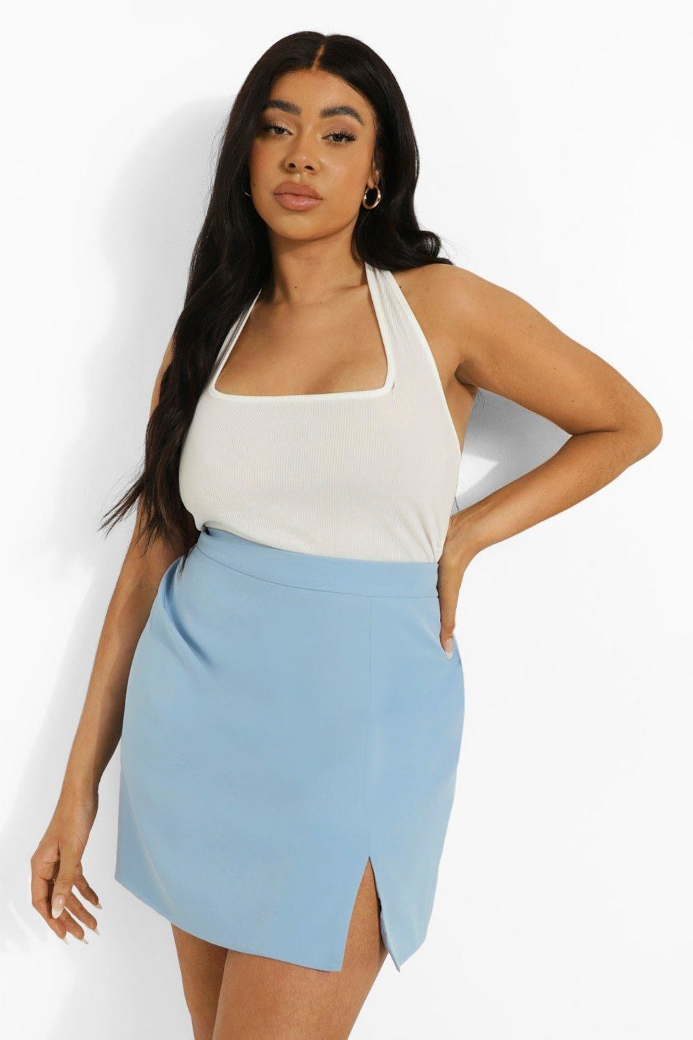a model wearing the blue skirt with a small slit in the leg with a white top