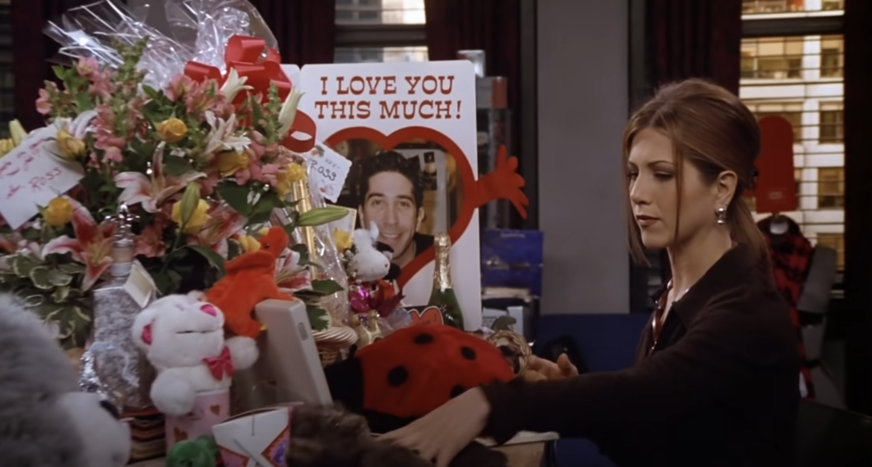 "Rachel from ""Friends"" working at her desk with a huge pile of gifts from her boyfriend Ross all over it"