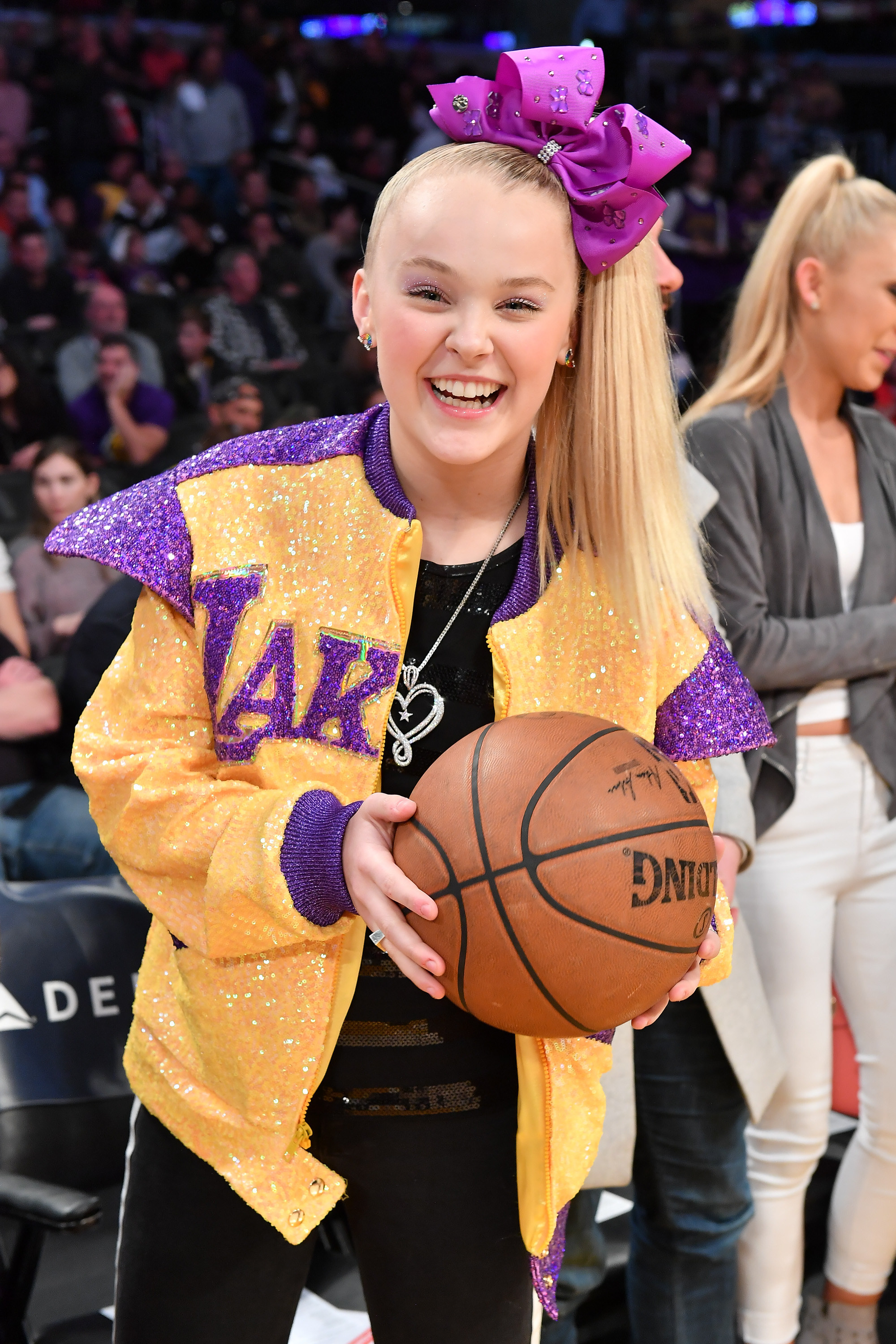 JoJo holding a basketball at a basketball game and wearing a glittered Lakers jacket