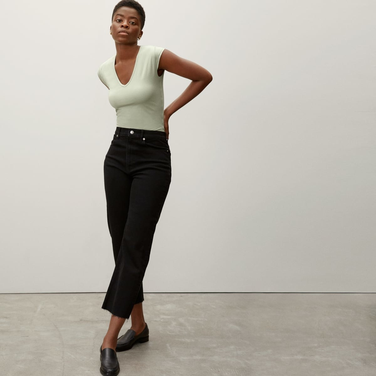 a modeal wearing the bodysuit in laurel green with black pants