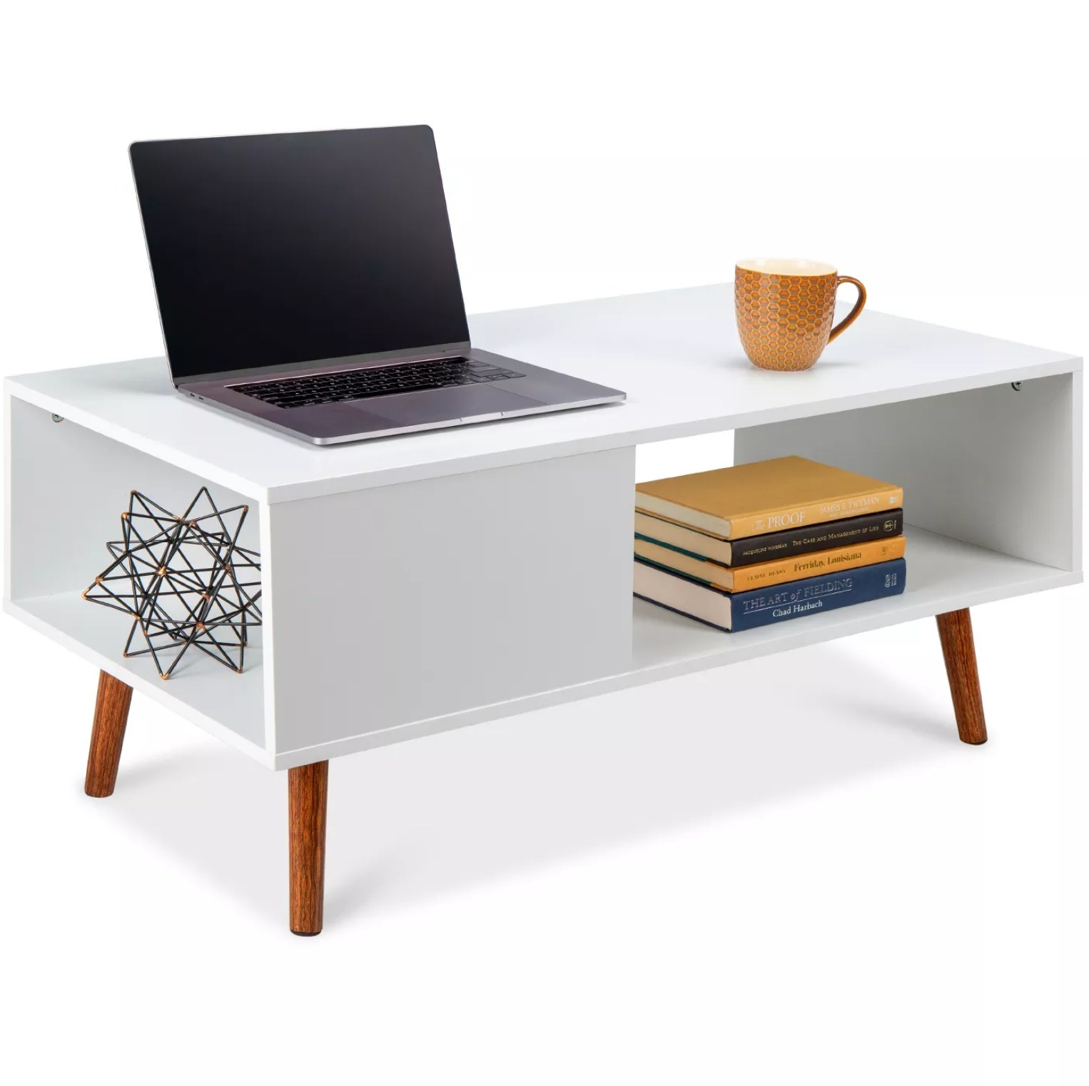 The white accent table with books, a laptop, and other decorations