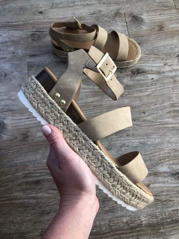 reviewer holding the shoes in tan