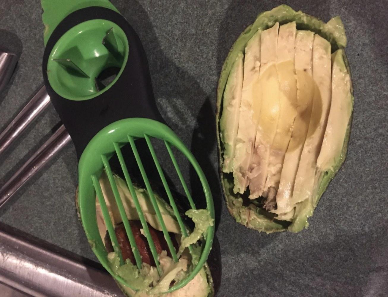 The avocado slicer next to an avocado