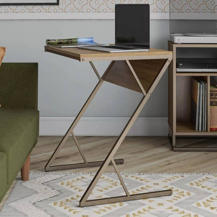 the brown accent table holding a laptop