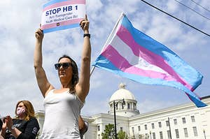 """A person stands in front of a trans pride flag and holds a sign reading """"Stop HB 1 Anti-Transgender Youth Medical Care Bill"""""""