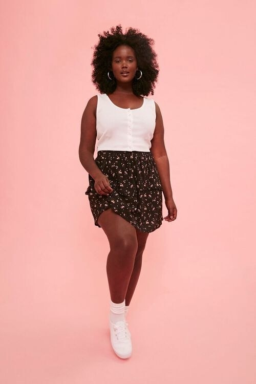Plus size model wearing the black floral skirt with sneakers and a tank