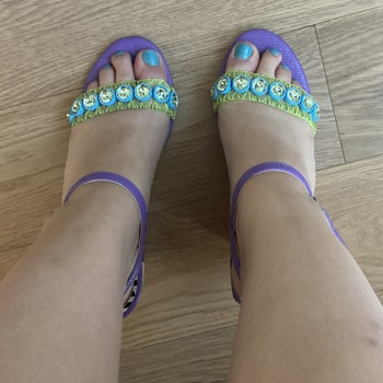 A view of my feet in the shoes from above, showing the sheer toe straps with green stitching and blue and clear jewels
