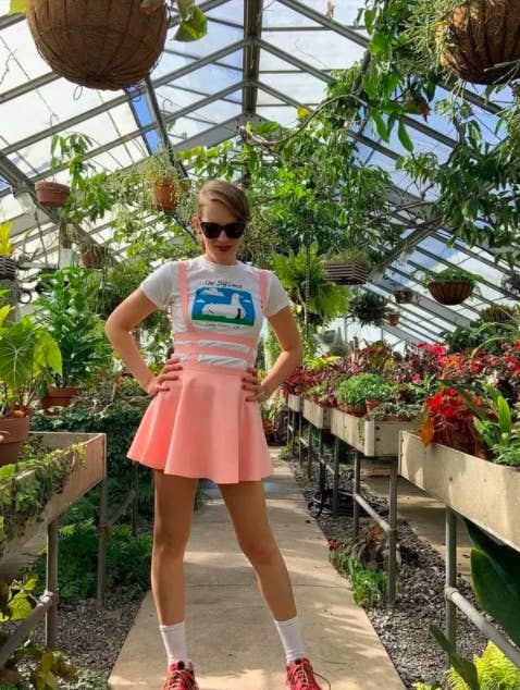 a person wearing the pink pinafore with a white graphic shirt inside of a greenhouse