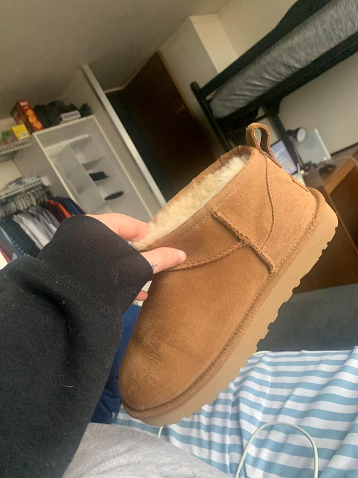 Reviewer holding Ugg boot