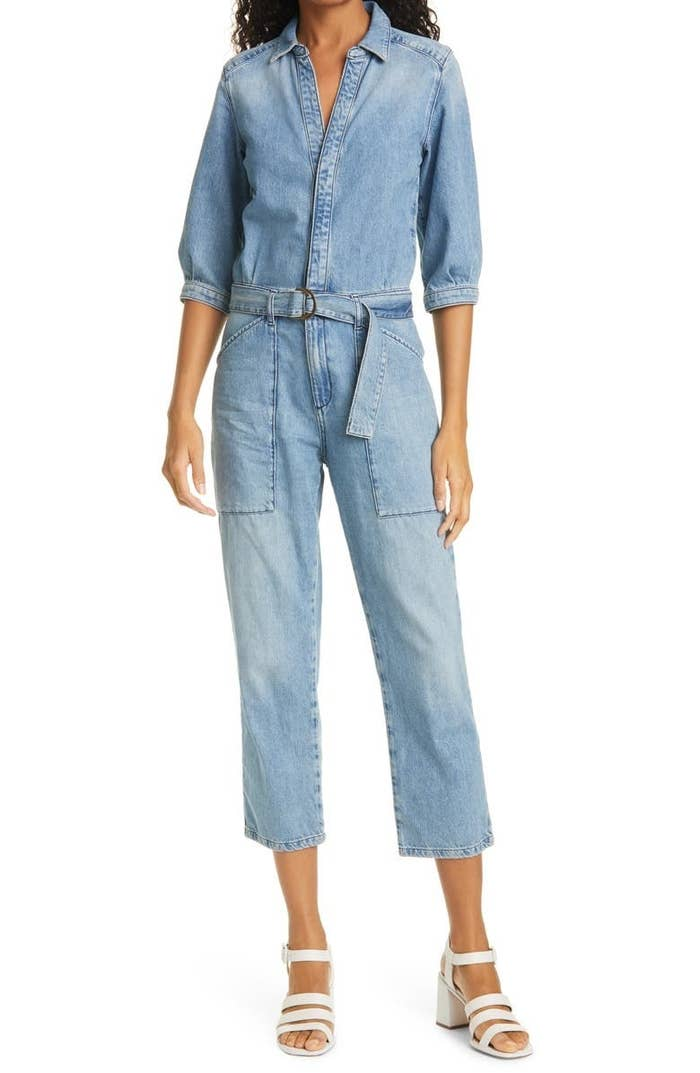 a model wearing the cropped denim jumpsuit with a looped belt and white heels