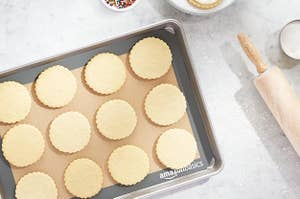 silicone baking mat on a sheet pan with sugar cookies on top