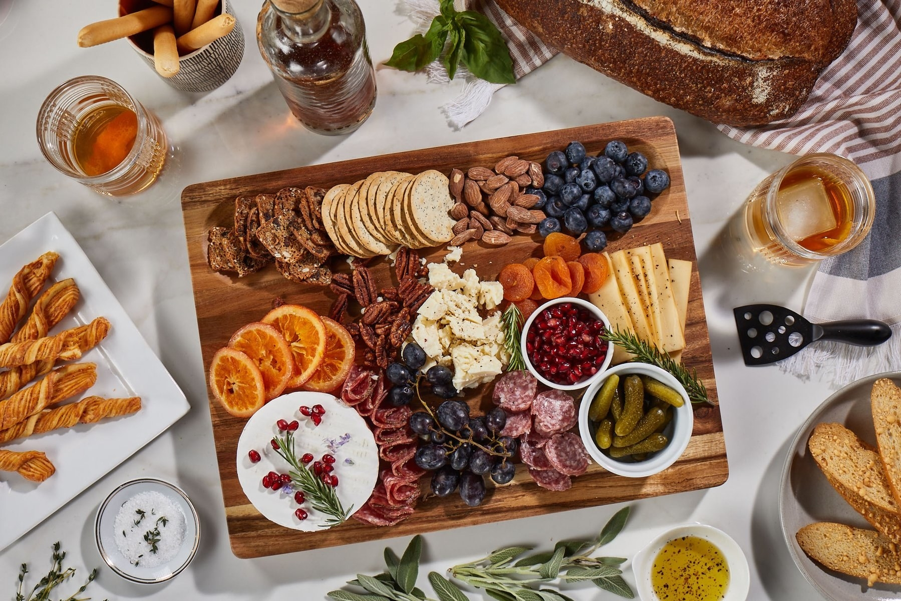the cutting board filled with cheese meats and fruit