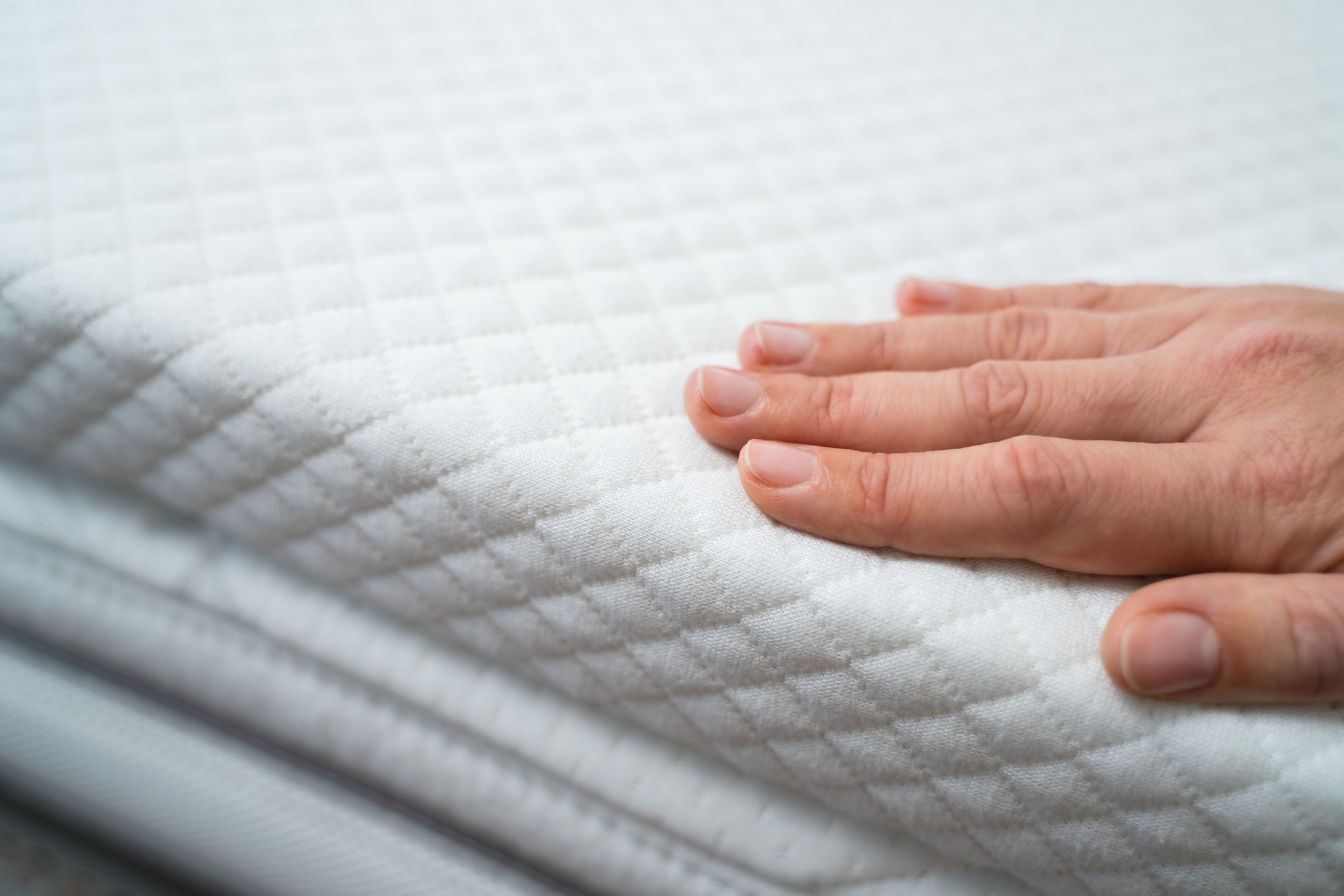 Hand on mattress stock image.