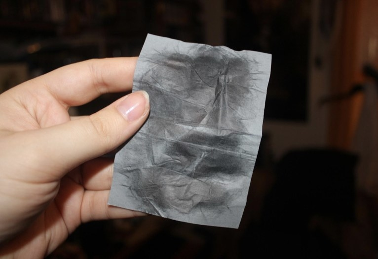 A hand holding a used blotting paper sheet