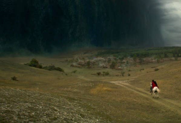 Someone on horseback rides through a green countryside; a dark shadowy wall of clouds called the Fold is ahead of them
