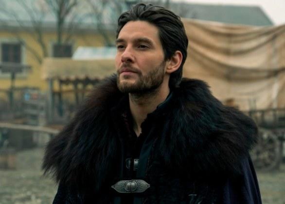 Kirigan wears a dark fur-trimmed cloak and stares at someone off camera.
