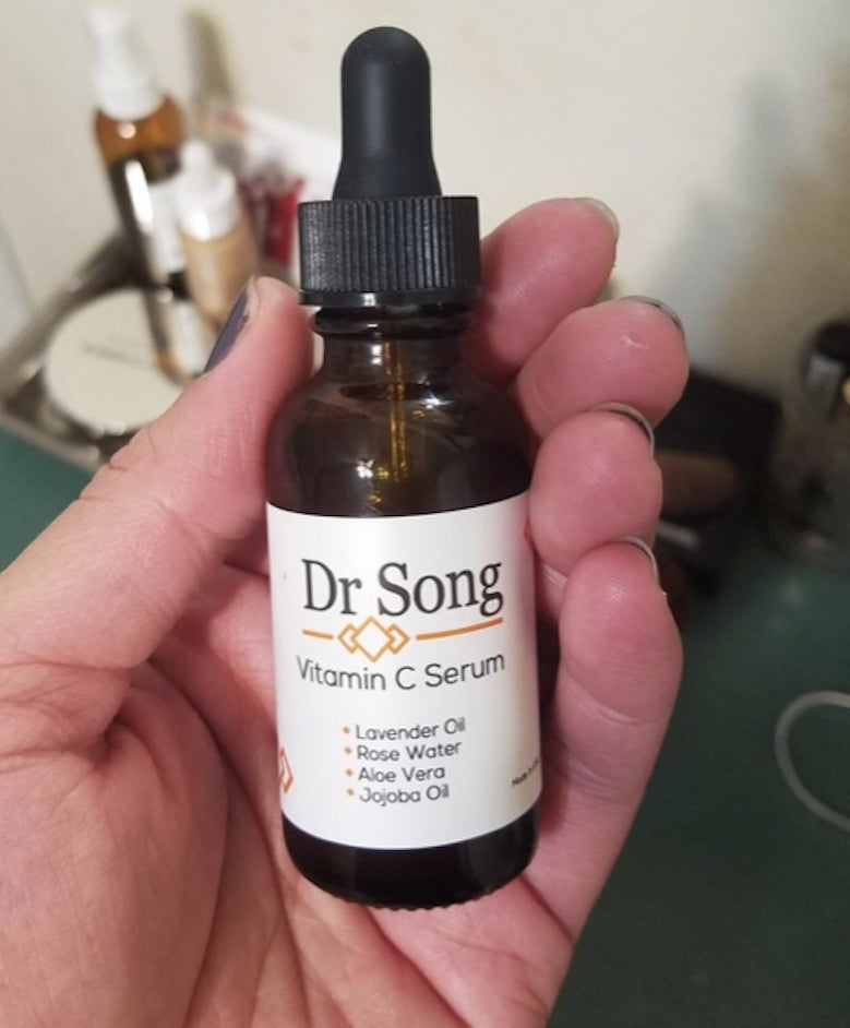 A hand holding a small bottle of face serum