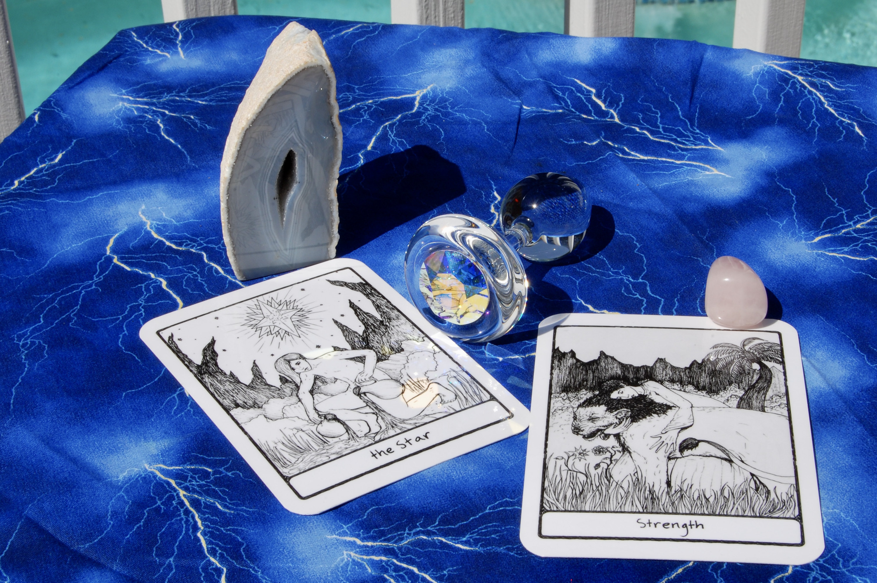 Photo of a Crystal Delights anal plug with two tarot cards (the Star and Strength), plus a geode and a small crystal