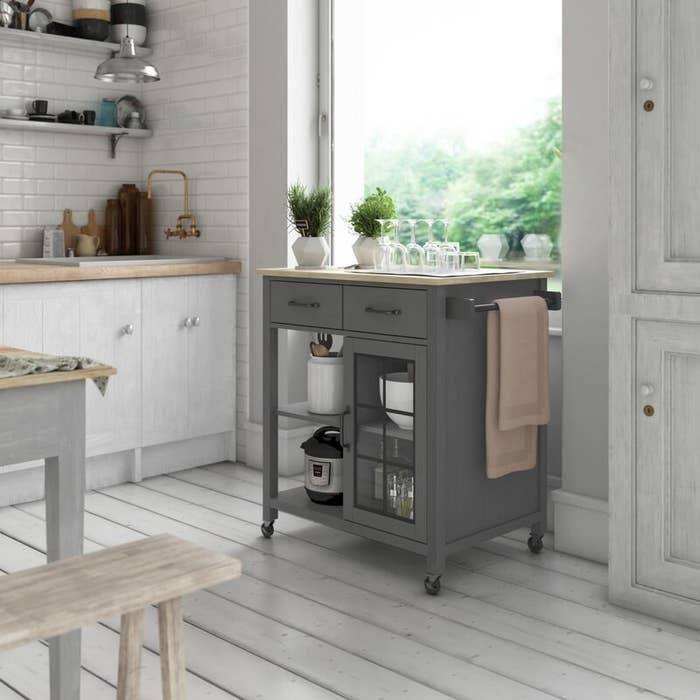 A grey, rolling kitchen cart with a wooden top, two drawers, and four shelves big enough to fit an InstantPot