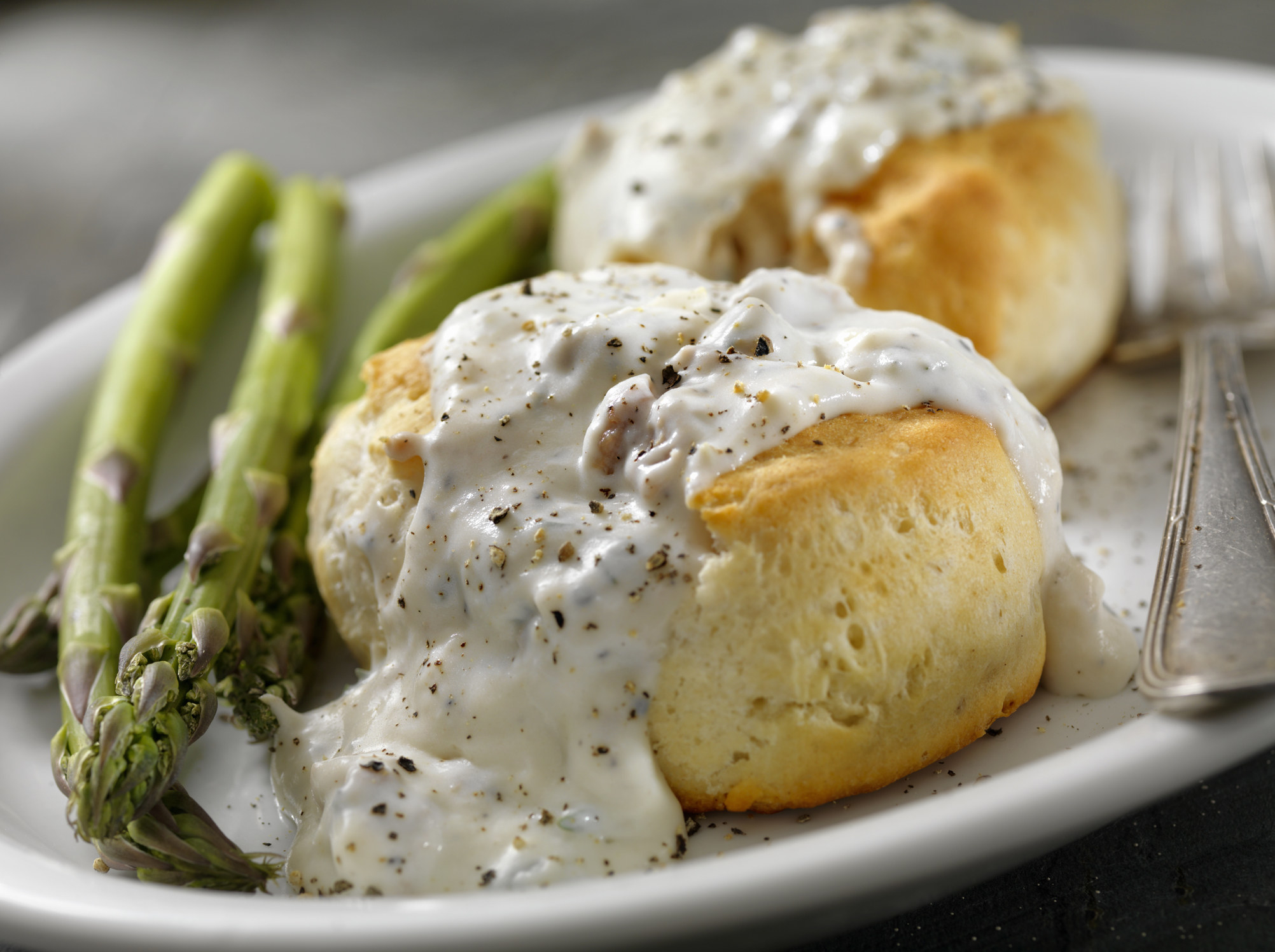 A plate of asparagus and biscuits with gravy