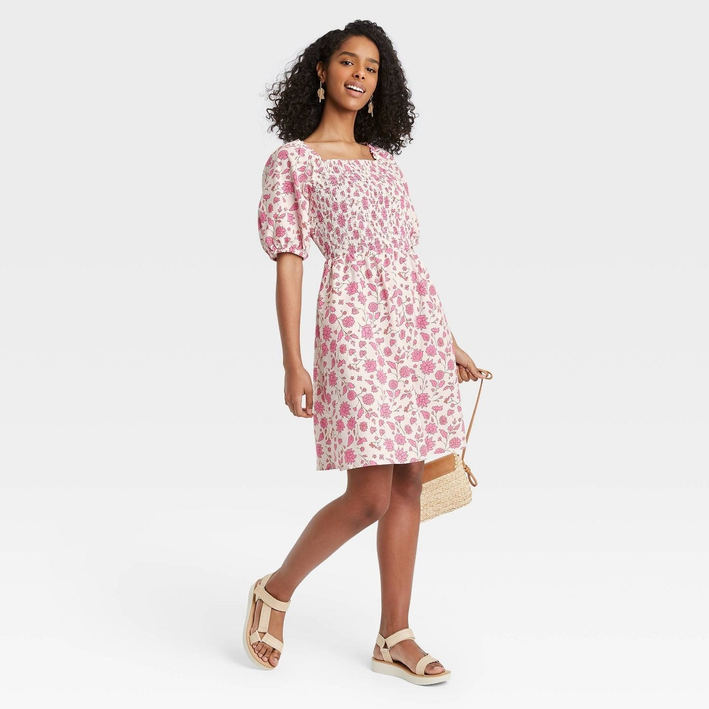Model wearing pink floral dress with cream background, stops above the knee