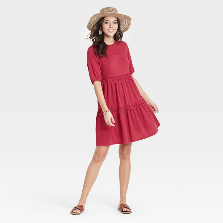 Model wearing red dress with a two tiered skirt, stop above the knee