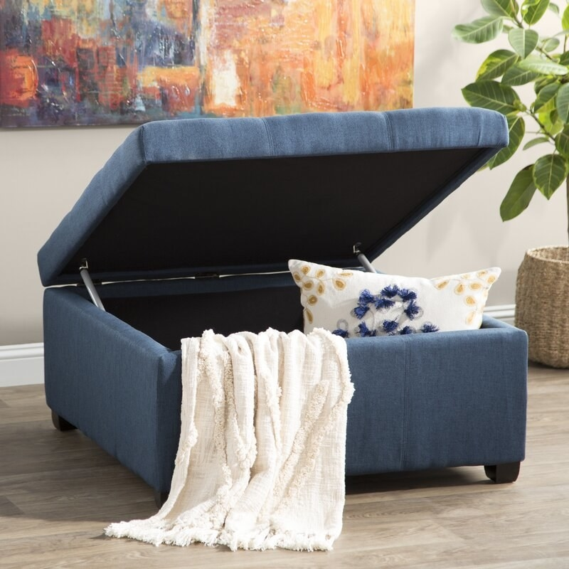 A dark blue, square ottoman with the top open displaying a pillow and blanket inside its storage feature
