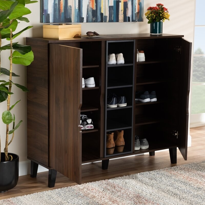 A brown wooden entryway cabinet that can hold up to twenty-five pairs of shoes in the 5 exterior shelves and 10 interior shelves behind the two doors