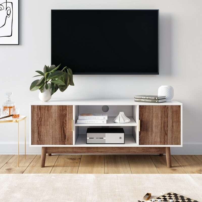 A white and rustic oak tv stand with 2 cabinets and 2 exterior shelves, filled with books, decor, and a stereo system
