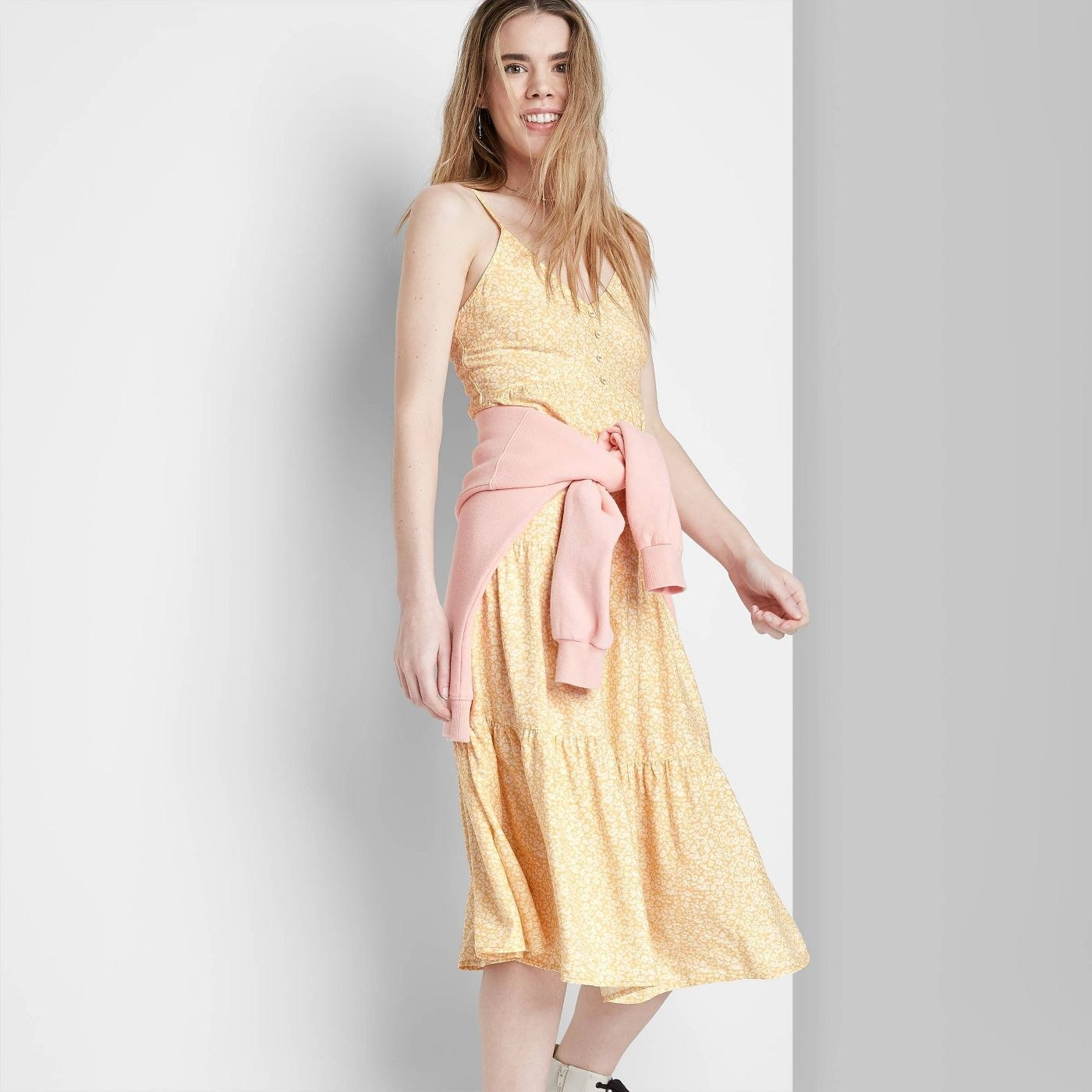 Model wearing yellow dress with light orange pattern
