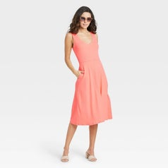 Model wearing coral midi dress with side pocket
