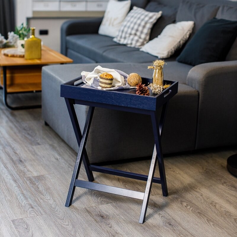 A blue wooden butler tray table with a removable tray feature so it can be used as both an end table and a serving tray