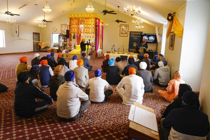 Members of the Sikh community wearing colorful dastār sit on the floor of a satsang listening to a speaker