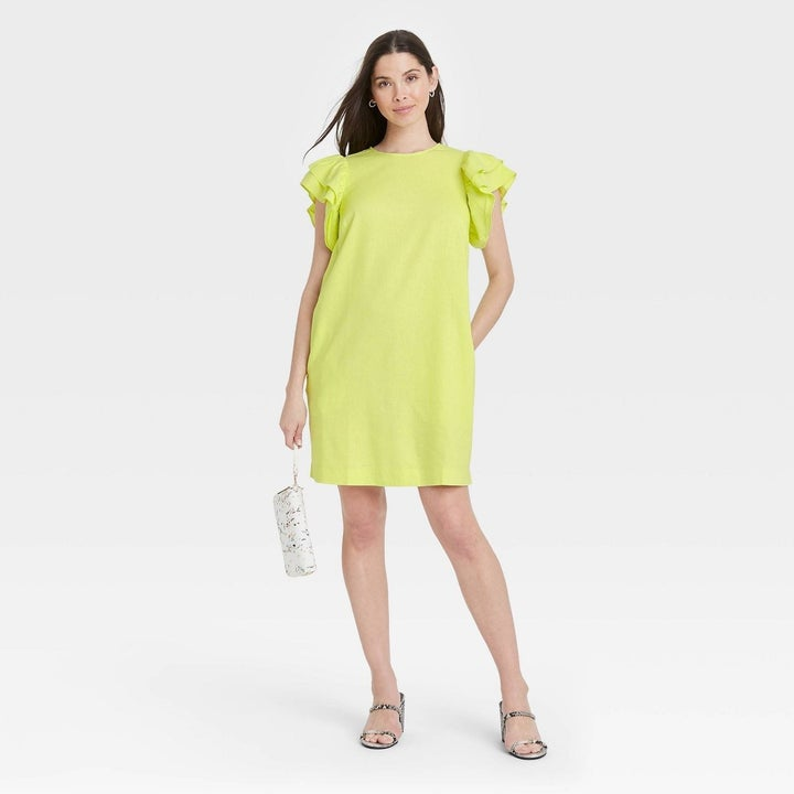 Model wearing  short sleeve dress with ruffle sleeves, goes past the thigh