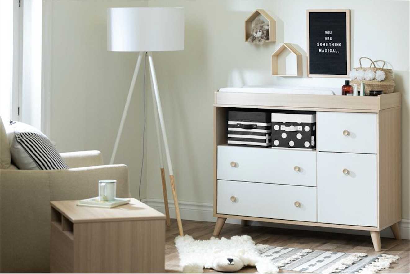 A white and soft elm dresser with a removable changing table top displayed in a nursery